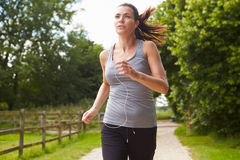 Woman Running In Countryside Wearing Earphones Royalty Free Stock Photos