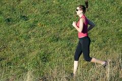 Woman running cross country Stock Photo