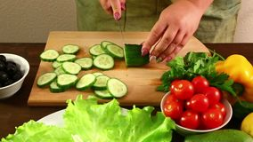 A woman is running a cucumber to prepare a vegetable salad. Shot with dolly from right to left stock video