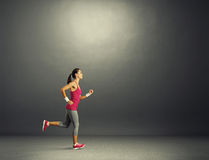 Woman running in the dark room Stock Image