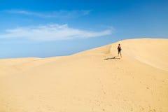 Woman running on desert dunes Royalty Free Stock Image