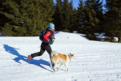 Woman running with dog in winter Royalty Free Stock Image