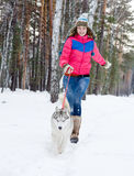 Woman running with dog in winter forest Stock Images