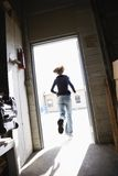 Woman running through doorway. Royalty Free Stock Image