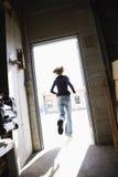 Woman running through doorway.