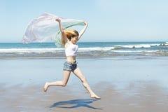 Woman running down the beach in summer season. Stock Photos