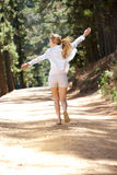 Woman running down country lane Stock Images