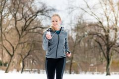 Woman running down a path on winter day in park. Woman running or jogging down a path on winter day in park Royalty Free Stock Images