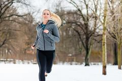 Woman running down a path on winter day in park. Woman running or jogging down a path on winter day in park Royalty Free Stock Photo