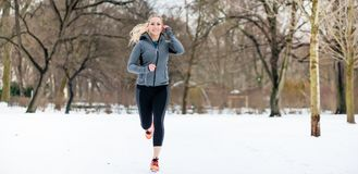 Woman running down a path on winter day in park stock image