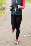 Woman running with dumbbells Stock Images