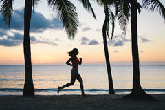 Woman running at dusk on tropical beach Stock Photo