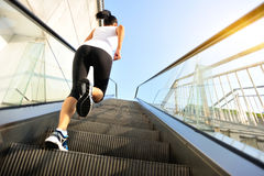 Woman running on escalator stairs Stock Photography