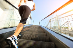 Woman running on escalator stairs Stock Images
