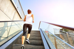 Woman running on escalator stairs Royalty Free Stock Images