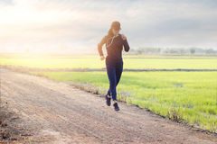 Woman running excercise on rural road of green field sunset back Royalty Free Stock Images
