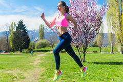 Woman running fast for sport on sunny day Royalty Free Stock Photos