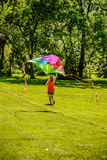Woman Running and Flying Colorful Kite Royalty Free Stock Photo