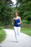 Woman running on footpath in the park Stock Image