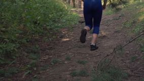 Woman is running in the forest. Athletic woman runs uphill in the forest, back view, slow motion stock footage