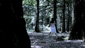 Woman running in forest scared stock video footage