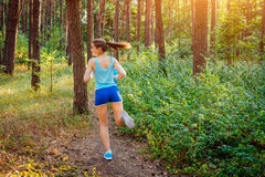 Woman running in the forest Stock Images