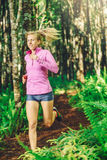 Woman Running on the Forrest trail Stock Photo