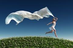 Woman running on the green grass beach Stock Photo