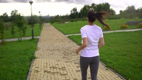 Young beautiful woman running in the Park. Taken from the back. slow-motion stock video