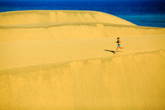 Woman running happy on beach and dunes Stock Photos