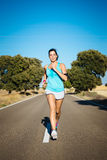 Woman running hard on countryside road Royalty Free Stock Images