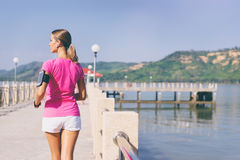 Woman running. Healthy lifestyle. Jogging outdoors. Young slim woman exercising on the sea pier Royalty Free Stock Images