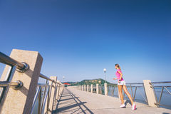 Woman running. Healthy lifestyle. Jogging outdoors. Young slim woman exercising on the sea pier Stock Photo