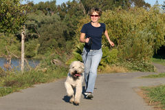 Woman running with her dog Stock Photo