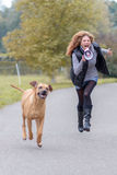 Woman running with her dog and a megaphone Stock Photos