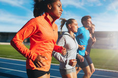 Woman running with her team on racetrack. Young african women running with her team on running track in stadium. Multiracial team of runner practicing at Stock Image