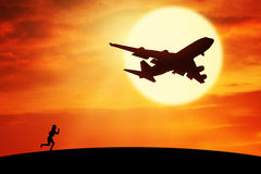 Woman running on the hill with flying plane Stock Photo