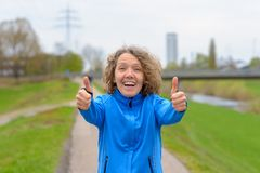 Woman in running jacket showing thumbs up royalty free stock photography