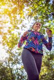 Woman running jogging along a forest, exercise and fitness concept. Young woman running jogging along a forest, exercise and fitness concept royalty free stock images