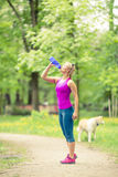 Woman running and jogging with dog in green summer park and wood Stock Photos
