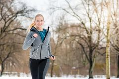 Woman running down a path on winter day in park stock photo