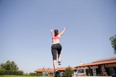 Woman running and jumping. A young woman running and jumping on a summer day on open doors Royalty Free Stock Images