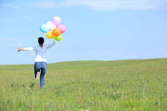 Woman running and jumping on green grassland with colored balloons Stock Photo