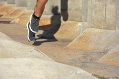 Woman running, jumping obstacles, without showing her face stock photo