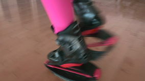 The woman running in kangoo shoes. Close-up. The camera focuses on the legs of the woman in black trousers. Sporty woman slowly walking in gym. The camera stock footage
