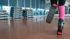 The woman running in kangoo shoes in the gym. Close-up. The camera focuses on the legs of the woman in black trousers. Sporty woman slowly walking in gym. The stock video footage