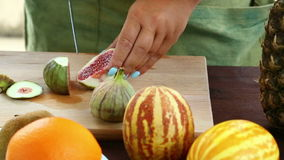 A woman is running a knife with figs, which is on a cutting board. stock footage