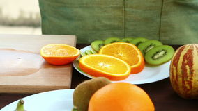 A woman is running a knife with an orange, which is on a cutting board. stock footage