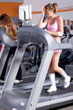 Woman on running machine in gym Stock Images