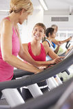 Woman On Running Machine In Gym Encouraged By Personal Trainer Stock Image